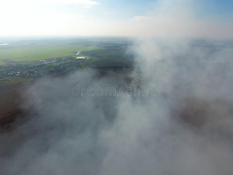 The smoke over the village. Clubs of smoke over the village houses and fields. Aerophotographing areas royalty free stock photo