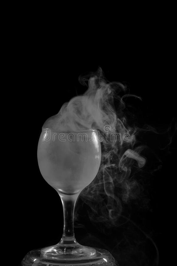 Smoke shisha in cocktail glass on a black background. royalty free stock photography