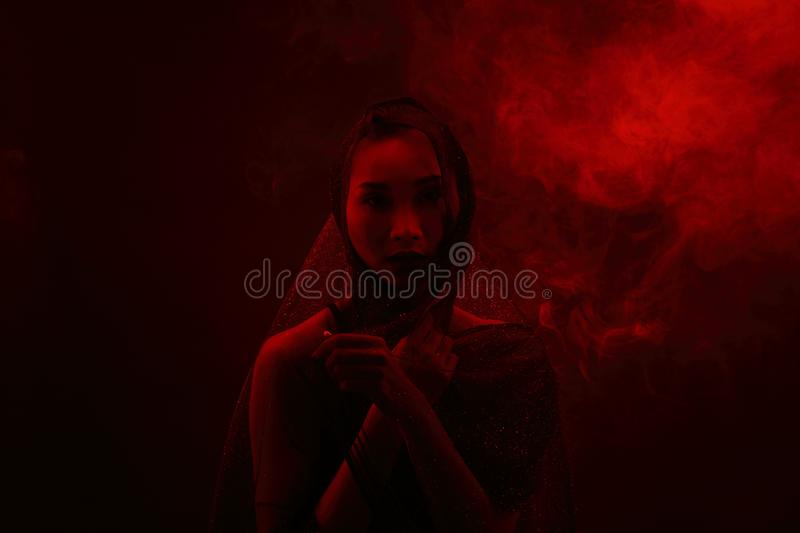 Smoke Tan Skin Asian Woman black hair dark lip with Dense Fluffy. Puffs of White Smoke and Fog on dark Background, Abstract Smoke girl mysterious Clouds, and royalty free stock photo