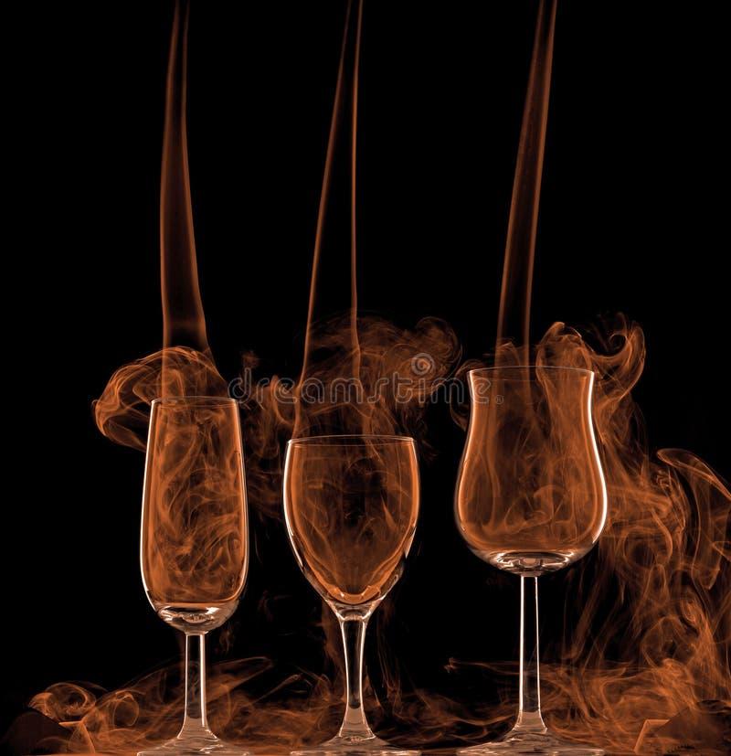 Smoke in wine glasses stock photos