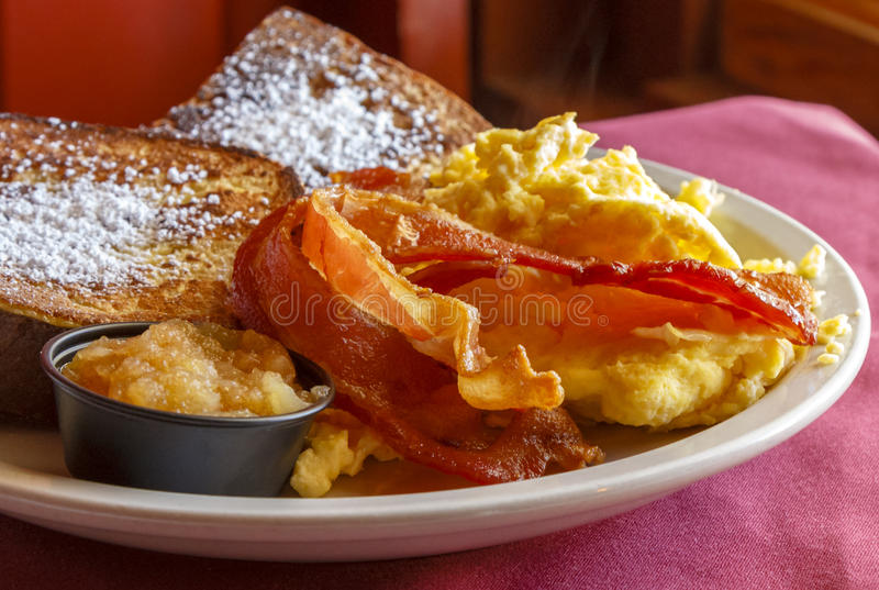 Smoked bacon and eggs. A delicious breakfast platter with thick-cut applewood smoked bacon, scrambled eggs, french toast and apple puree royalty free stock photography