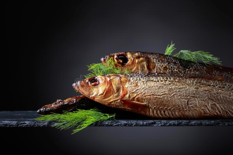 Smoked Baltic herring with dill on a black background. stock image