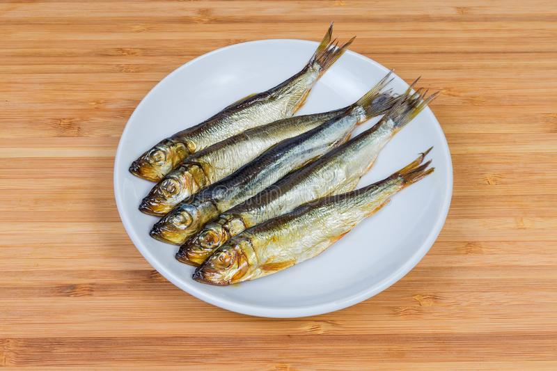 Smoked baltic herring on the saucer stock photos