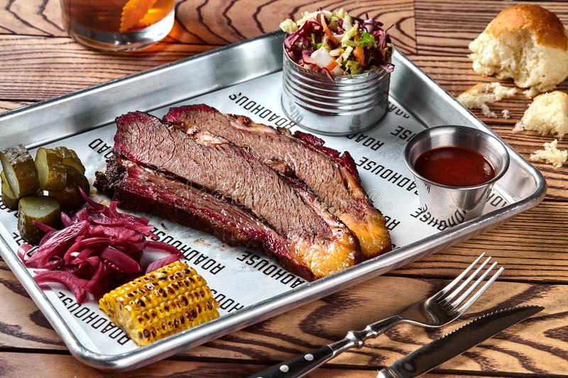 Smoked barbecue beef brisket with sauce, corn, marinated cucumber and onions royalty free stock images