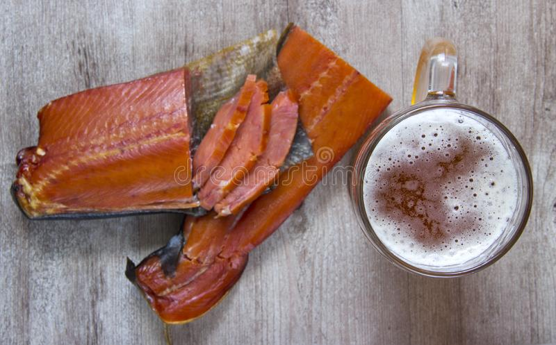 Smoked fish and a glass of beer on a wooden background stock image