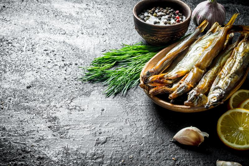 Smoked fish with herbs, lemon and spices royalty free stock photography