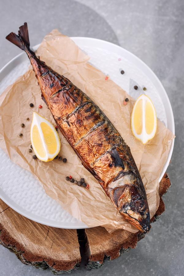 Smoked fish with lemon slices and pepper on backing paper on wooden smoking background, top view. Smoked fish with lemon slices and pepper on backing paper on royalty free stock images