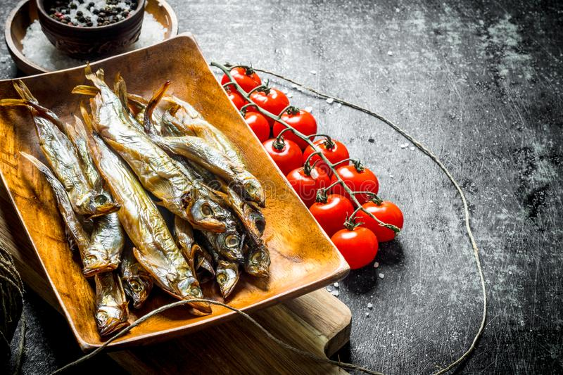 Smoked fish with tomatoes and spices royalty free stock image