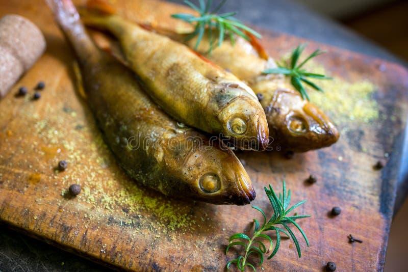 Smoked flavored peixes em uma placa com fundo do spiceson imagens de stock royalty free