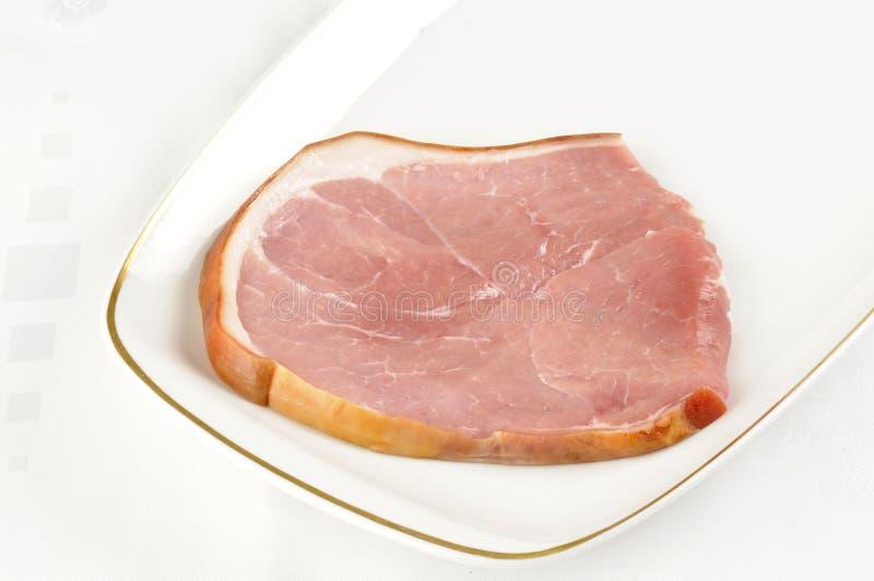 Smoked Gammon steak. A raw smoked gammon steak on a white plate royalty free stock image