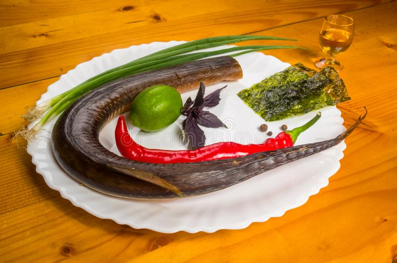 Smoked garfish with lime, Basil, green onions, chili, nori chips, spices, olive oil in a white ceramic dish, on a wooden royalty free stock photography