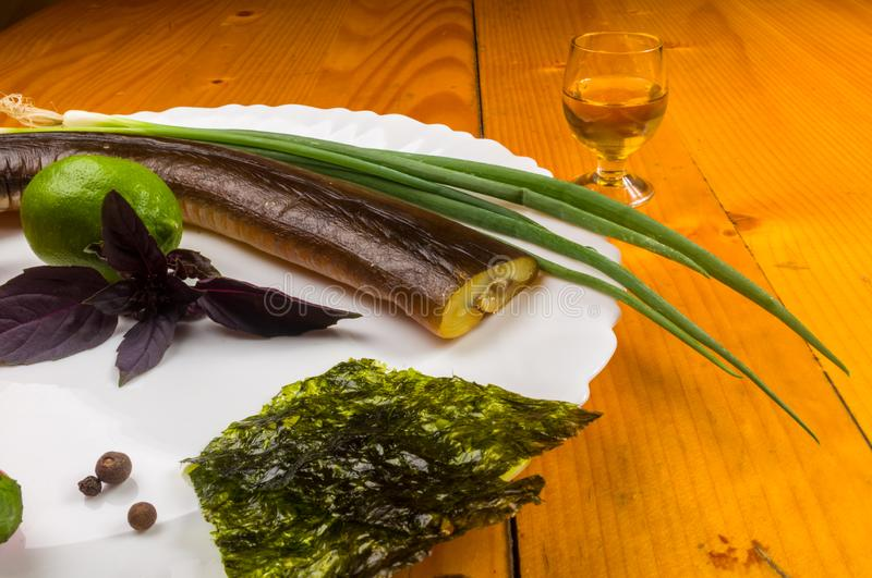 smoked garfish with lime, Basil, green onions, chili, nori chips, spices, olive oil in a white ceramic dish, on a wooden table royalty free stock photo