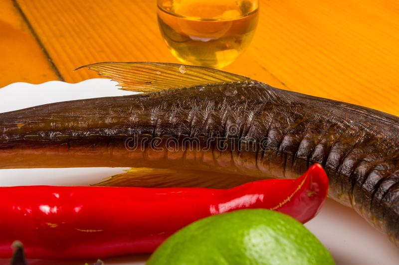 smoked garfish with lime, Basil, green onions, chili, nori chips, spices, olive oil in a white ceramic dish, on a wooden table royalty free stock photos