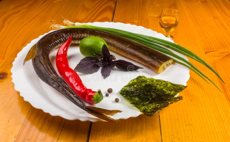 smoked garfish with lime, Basil, green onions, chili, nori chips, spices, olive oil in a white ceramic dish, on a wooden table royalty free stock photography