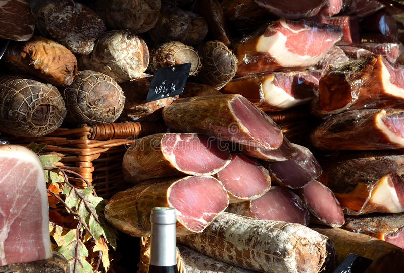 Smoked ham. And sausages products on a shop display. Foreground with the neck of a white wine bottle royalty free stock photo