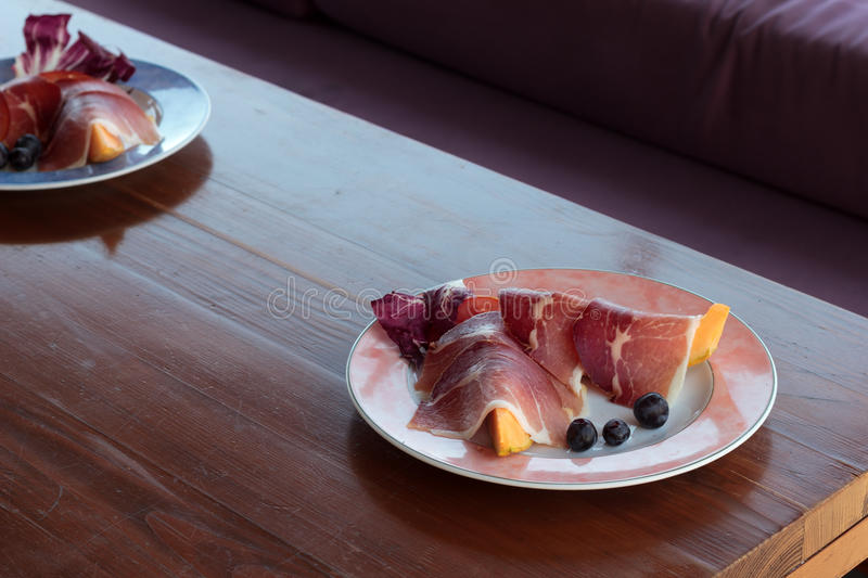 Smoked ham and musk melon stock image