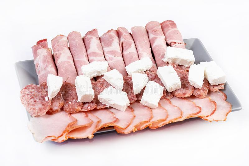 Smoked ham served with white cheese on the plate. Snack, appetizer, food, gourmet, background, cuisine, meat, bacon, rustic, isolated, pork, grape, italian stock image