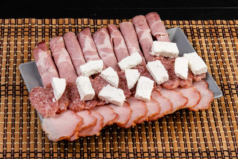 Smoked ham served with white cheese on the plate. Snack, appetizer, food, gourmet, background, cuisine, meat, bacon, rustic, isolated, pork, grape, italian royalty free stock photo