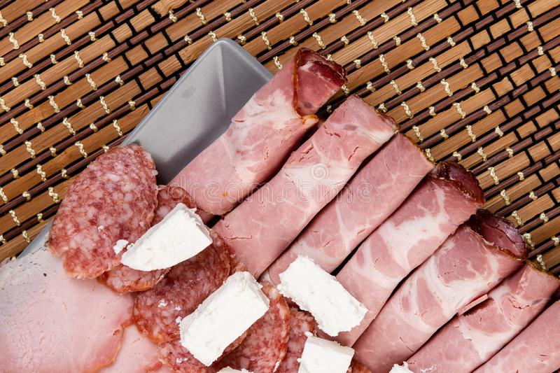 Smoked ham served with white cheese on the plate. Snack, appetizer, food, gourmet, background, cuisine, meat, bacon, rustic, , pork, grape, italian, slice royalty free stock photo