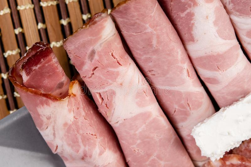 Smoked ham served with white cheese on the plate. Snack, appetizer, food, gourmet, background, cuisine, meat, bacon, rustic, , pork, grape, italian, slice royalty free stock images