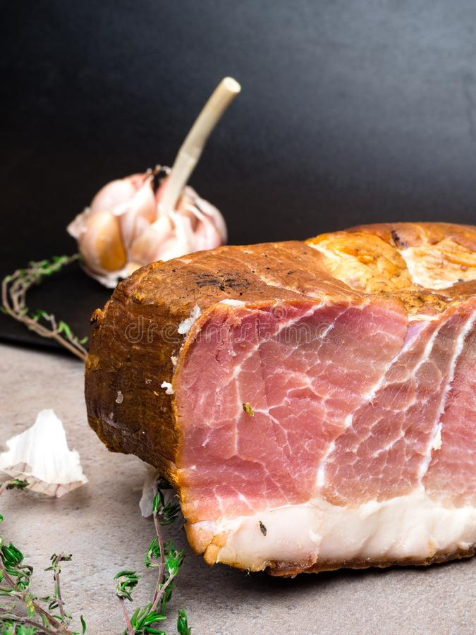 Smoked ham on a stone table with addition of fresh aromatic herbs and spices. Natural product from organic farm, produced by. Traditional methods, free space stock photos
