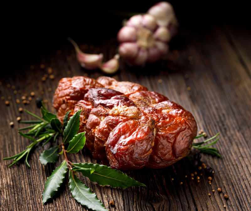 Smoked ham on a wooden rustic table with addition of fresh aromatic herbs. Smoked ham on a wooden rustic table, natural product from organic farm, produced by stock photo