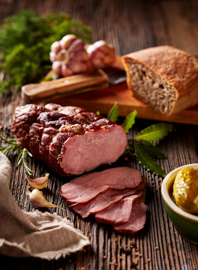Smoked ham on a wooden rustic table with addition of fresh aromatic herbs and spices.Table set with traditional regional products. Smoked ham sliced on a wooden stock photos