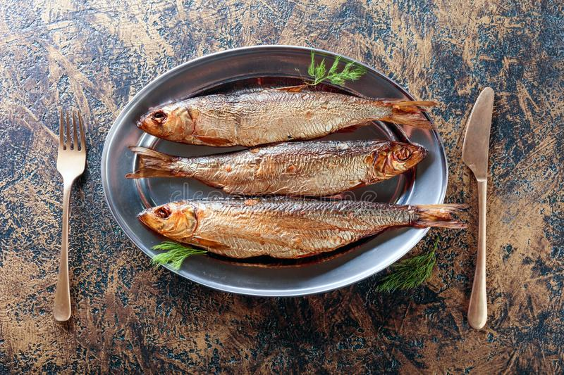 Smoked herring with dill. On a metal dish. Copy space for your text royalty free stock photography