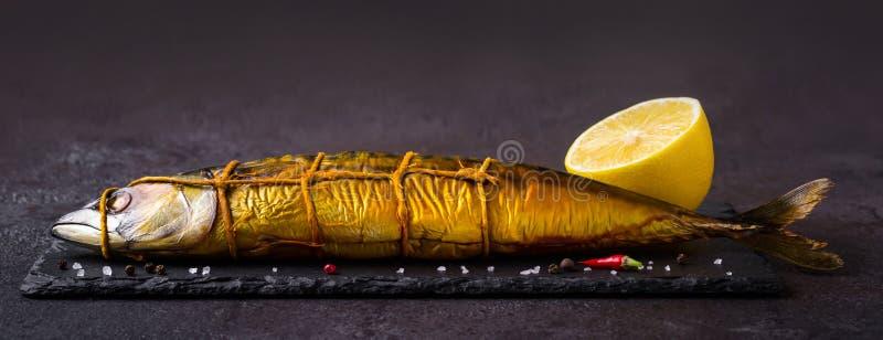 Smoked mackerel fish on black stone cutting board, banner format stock image