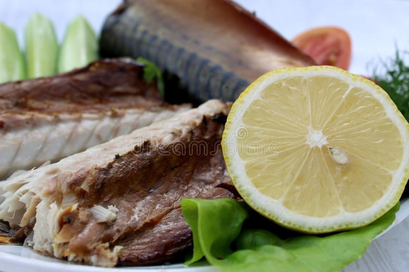 Smoked mackerel on a plate. mackerel with lemon and vegetables royalty free stock images
