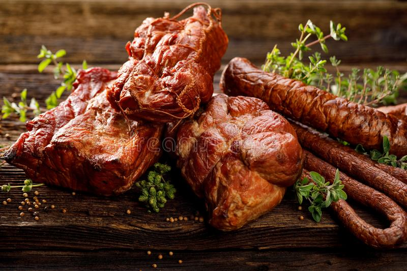 Smoked meats and sausages. A set of traditional smoked meats and sausages: ham,gammon, pork loin, home-style sausages, kabanosy. Traditional meats and sausages royalty free stock images