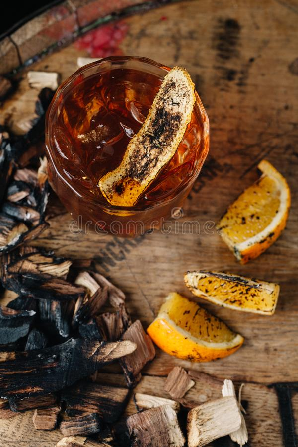 Smoked old fashioned cocktail on dark wooden background. Smoked old fashioned cocktail garnished with an orange peel on dark wooden background royalty free stock photo