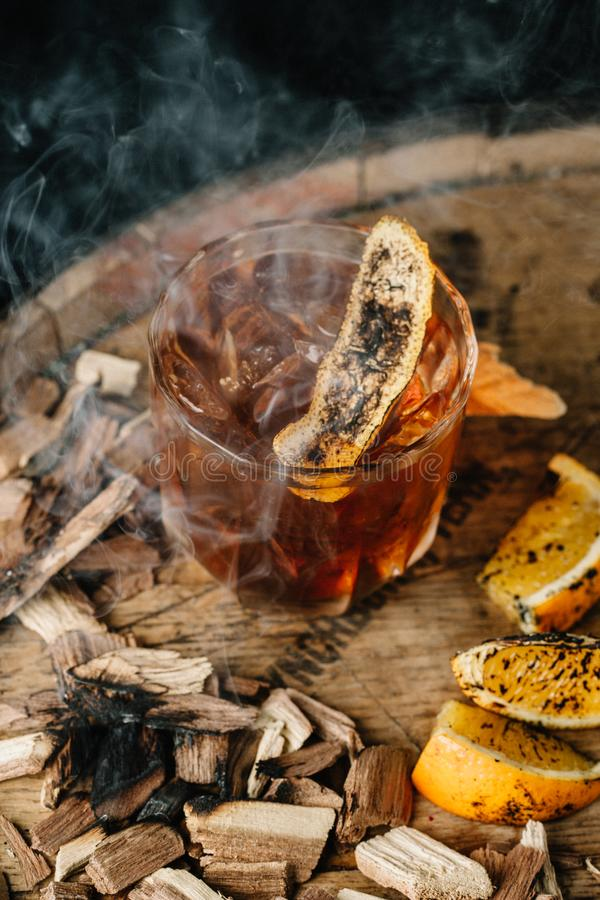 Smoked old fashioned cocktail on dark wooden background. Smoked old fashioned cocktail garnished with an orange peel on dark wooden background stock photography