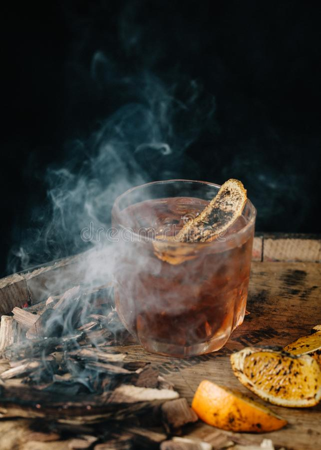 Smoked old fashioned cocktail on dark wooden background. Smoked old fashioned cocktail garnished with an orange peel on dark wooden background stock photo