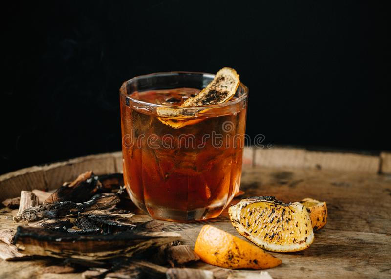 Smoked old fashioned cocktail on dark wooden background. Smoked old fashioned cocktail garnished with an orange peel on dark wooden background royalty free stock photos