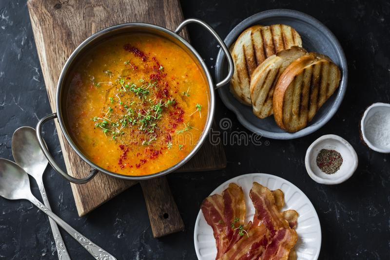 Smoked paprika lentil soup with grilled cheese sandwiches and crispy bacon on a dark background, top view. Delicious comfort food stock image