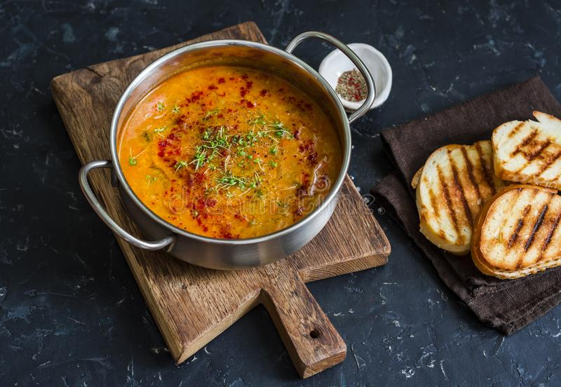 Smoked paprika vegetarian lentil soup with grilled cheese sandwiches a dark background, top view. Delicious comfort food concept stock image