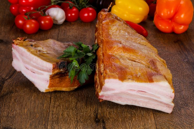 Smoked pork meat. Over the wooden background royalty free stock photography