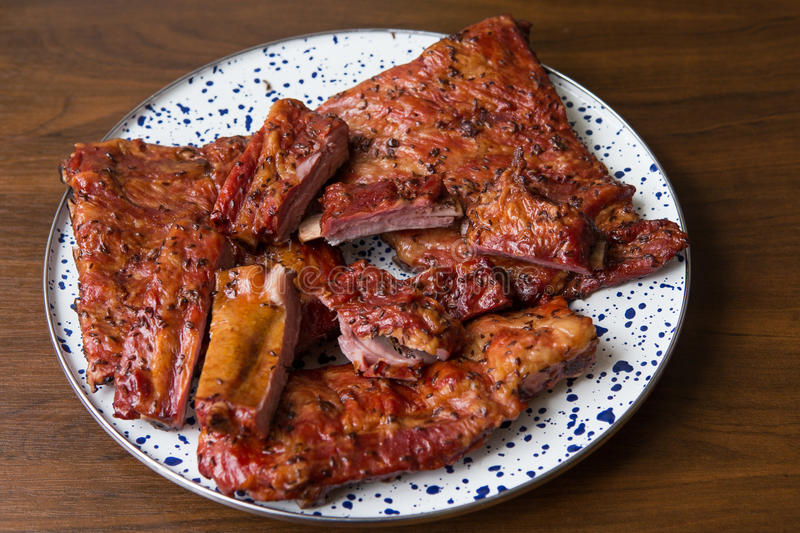 Smoked pork ribs on a decorative plate. Food and cooking. Smoked pork ribs on a decorative plate -sliced pieces. Food and cooking royalty free stock images