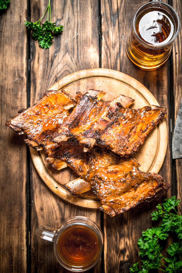 Smoked ribs grilled with beer and parsley. On a wooden table stock image