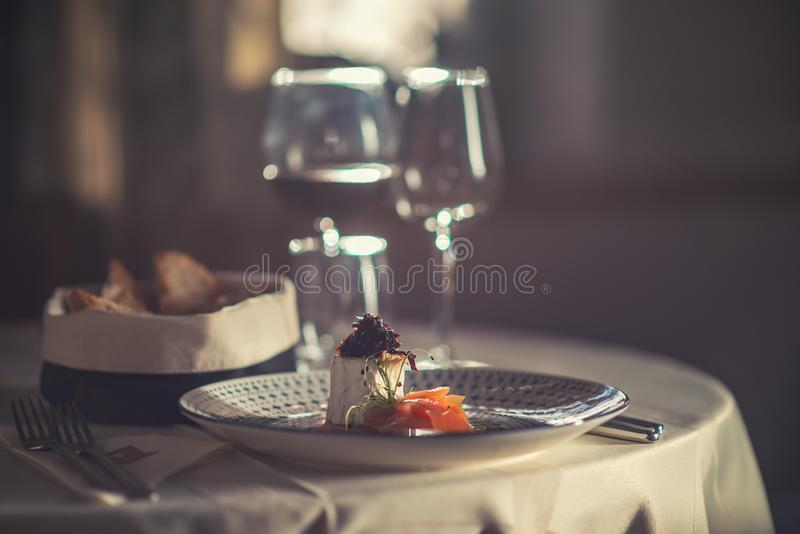 Smoked salmon with cheese, onion and herbs served on plate with glass of wine and toast, modern gastronomy.  royalty free stock image