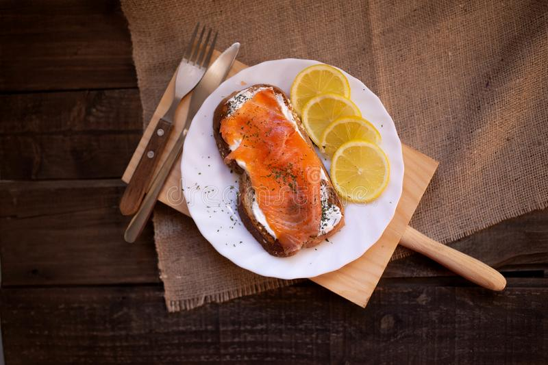 Smoked salmon with cheese toasted bread lemon and yogurt dip. Smoked salmon with toasted bread lemon and yogurt dip for breakfast stock image