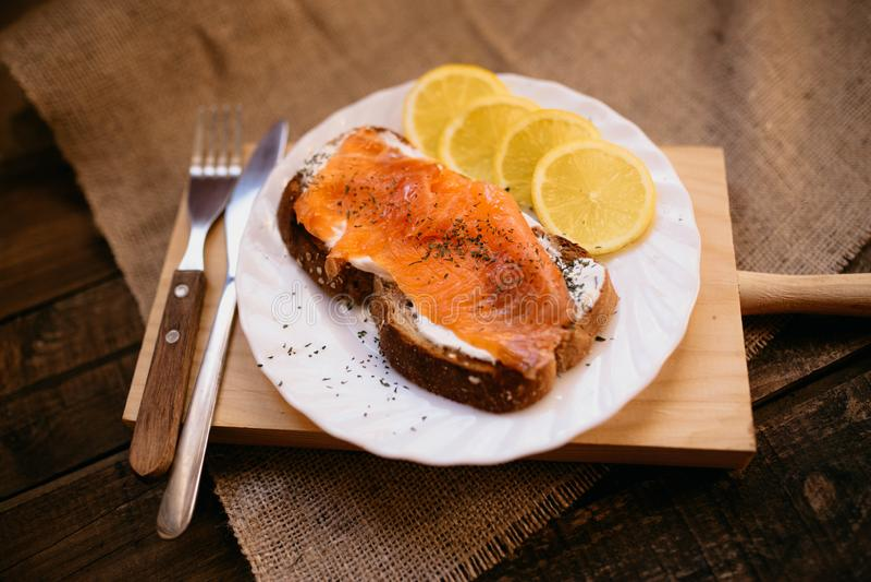 Smoked salmon with cheese toasted bread lemon and yogurt dip. Smoked salmon with toasted bread lemon and yogurt dip for breakfast royalty free stock photos
