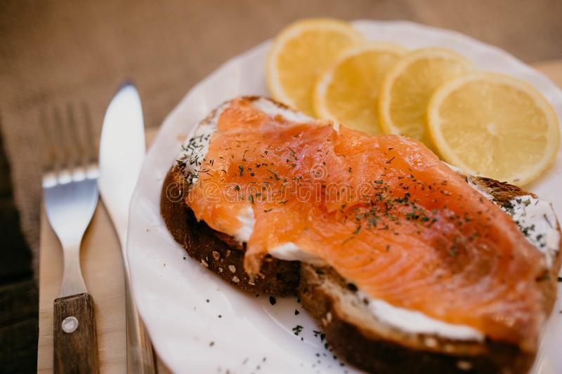 Smoked salmon with cheese toasted bread lemon and yogurt dip. Smoked salmon with toasted bread lemon and yogurt dip for breakfast stock photos