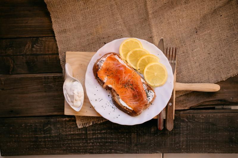 Smoked salmon with cheese toasted bread lemon and yogurt dip. Smoked salmon with toasted bread lemon and yogurt dip for breakfast royalty free stock image