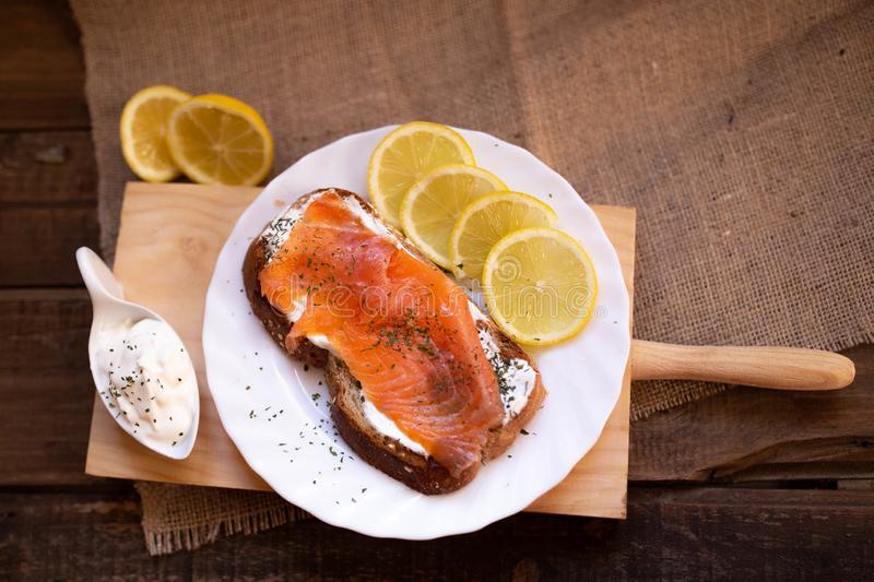 Smoked salmon with cheese toasted bread lemon and yogurt dip. Smoked salmon with toasted bread lemon and yogurt dip for breakfast stock images