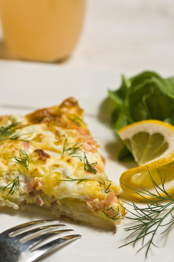 Smoked salmon frittata. Baked Smoked salmon frittata on a white plate with lettuce, dill, lemon slice , grapefruit juice, and a silver fork royalty free stock photo
