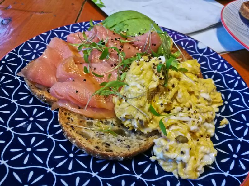 Smoked salmon and healthy scramble eggs on brown hard toast in a cafe stock photography