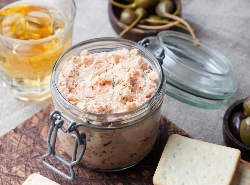 Smoked salmon and soft cheese spread, mousse, pate in a jar with crackers and capers on a wooden background. Smoked salmon and soft cheese spread, mousse, pate royalty free stock photos