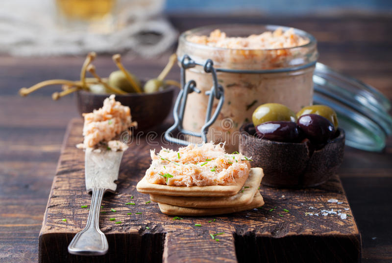Smoked salmon and soft cheese spread, mousse, pate in a jar with crackers and capers on a wooden background. Smoked salmon and soft cheese spread, mousse, pate royalty free stock images